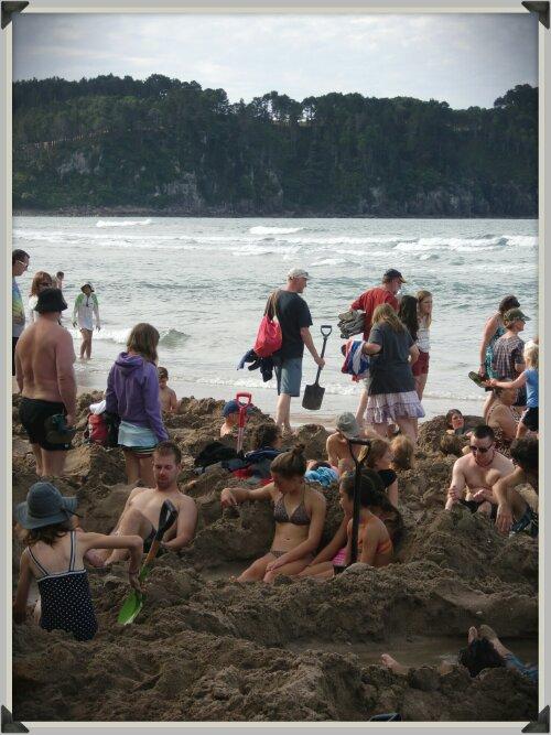 Touristes armés de pelles sur la plage de Hot Water Beach